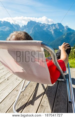 Young man relaxing in mountain resort. Enjoying view of Brenta group above Madonna di Campiglio.