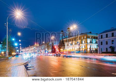 Minsk, Belarus - November 3, 2016: Night View Of Cathedral of Saint Virgin Mary And Building of French Embassy in Republic of Belarus. Traffic On Illuminated Pobedtiley Avenue Street In Minsk, Belarus.
