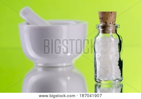 homeopathic pills in a glass bottle with mortar green background