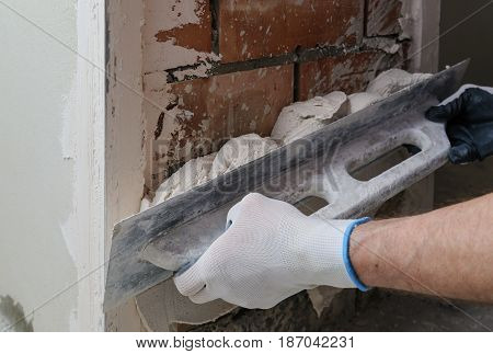 Worker's hands are using long trowel for gypsum plaster.