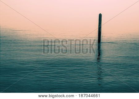 Calm water with solitary wooden post and reflection. Simple serene image with connotations of Zen Buddhism.