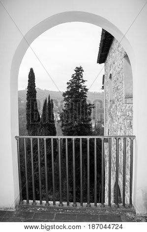 View of trees and building wall from an arch. Florence. Italy. Photo in black and white color style.