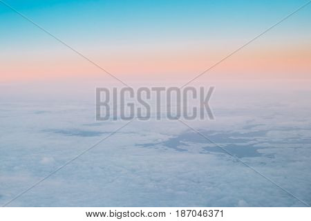 Aerial View From High Altitude Flight Of Aircraft On Snow-covered Ground In Winter At Sunset Sunrise. Forests And Fields. Clear Sunny Dawn Sky With Cold And Warm Colors.