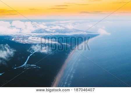 Western Dvina Flows Into The Baltic Sea. River Divides The Northern And Kurzeme District Of Riga, Latvia. View From Airplane Flight. Sunset Sunrise Over Gulf Of Riga, Bay Of Riga, Or Gulf Of Livonia