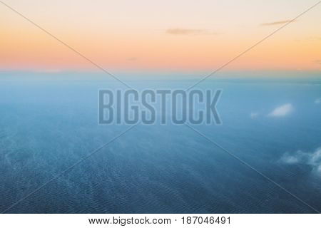 Aerial View From High Altitude Flight Of Aircraft On Sea Ocean Surface In Winter At Sunset Sunrise. Clear Sunny Dawn Sky With Cold And Warm Colors.