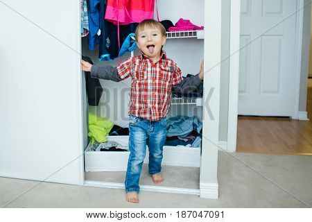 Candid natural portrait of funny cute white Caucasian little boy toddler in wardrobe at home making funny face showing tongue lifestyle documentary style