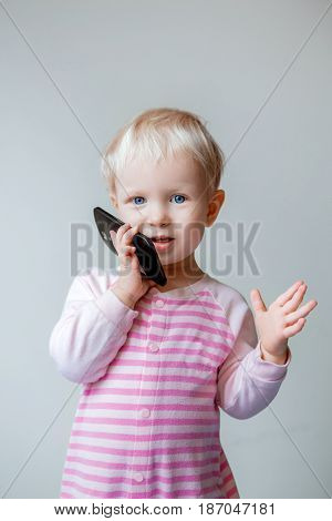 Cute adorable white Caucasian blond baby with blue eyes talking over mobile cell phone with funny expression on her face
