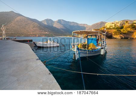 Village Bali Island Crete Greece - June 24 2016: Beautiful morning scenery with mountains bay of Mediterranean sea and a pier with fishing boat with net.