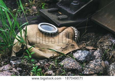 Ragged gas mask among stones and grass  near railroad