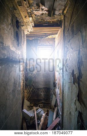 Destroyed room and bright light from little window in ruined abandoned building, vertical photo