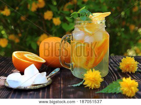 orange lemonade with ice cubes and flowers