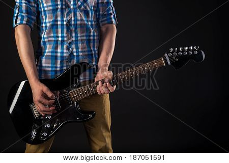 Music And Art. The Guitarist Holds An Electric Guitar In His Hands, On A Black Isolated Background.