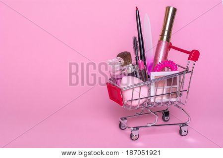 Shopping trolley with makeup on a pink background. Perfume, sponge, brush, mascara, pencil, nail file, eye shadow, lip gloss in the basket