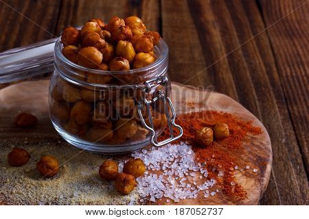 Roasted spicy chickpeas with salt, garlic and paprica on rustic background