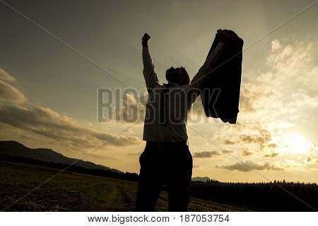 Silhouette of a businessman raising his arm while looking up the sky for success.