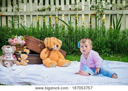 Little girl sitting on white coverlet in the summer garden.