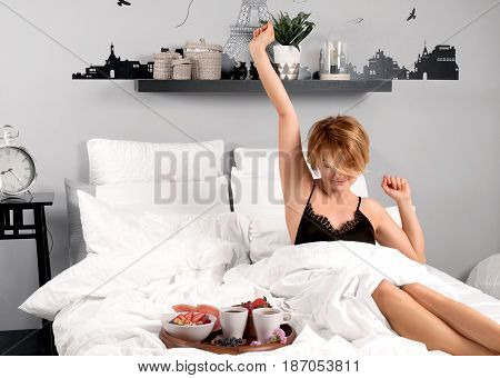 Breakfast. Beautiful woman stretching in bed after wake up.