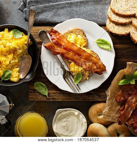 Big breakfast with bacon, bagels and scrambled eggs on toast overhead