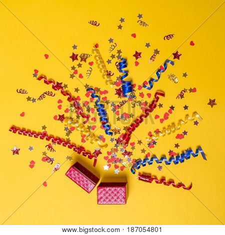 Creative concept with festive decor on yellow background. Confetti hearts and stars red yellow blue ribbons fly out of the red gift box. Explosion of confetti.