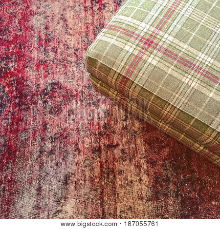 Checked textile hassock on a red vintage style carpet.