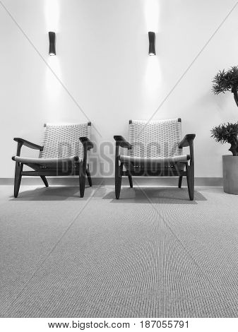 Black and white interior with rattan chairs and carpet floor.