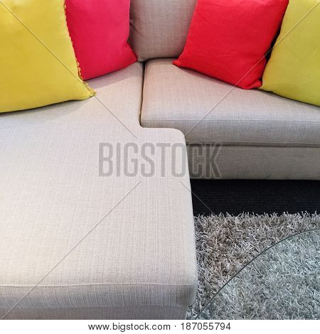 Bright red and yellow cushions decorating gray corner sofa.