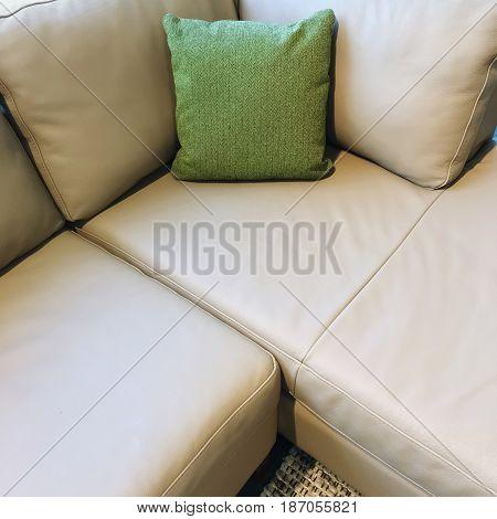 Gray corner sofa decorated with green cushion. Modern design.