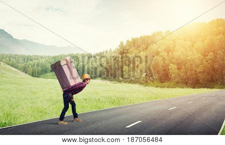 Man carrying on his back large box