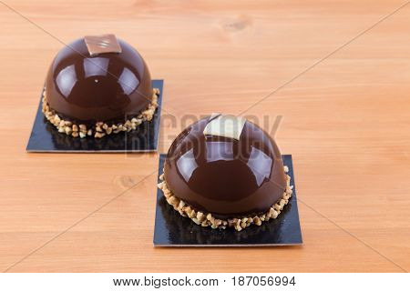 Two Shine Mini Round Chocolate Cakes With Crust On An Oak Natural Wood Table