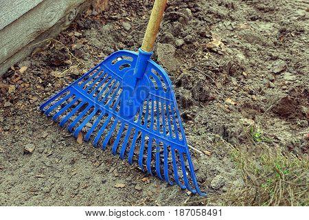 Blue plastic rake rake in the yard