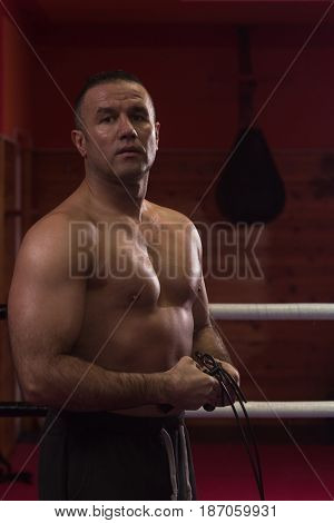 portrait of muscular professional kickboxer who standing in the ring while training for the fight