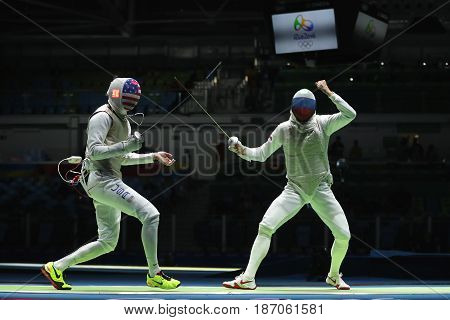 RIO DE JANEIRO, BRAZIL - AUGUST 12, 2016: Fencer of Team USA (L) competes against Team Russia fencer in the Men's team foil of the Rio 2016 Olympic Games at the Carioca Arena 3