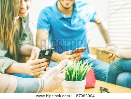 Group of friends using mobile smartphone browsing on internet social media - Young generation addicted - Students surfing online using phones - Cold filter - Focus on male hand with tattoo