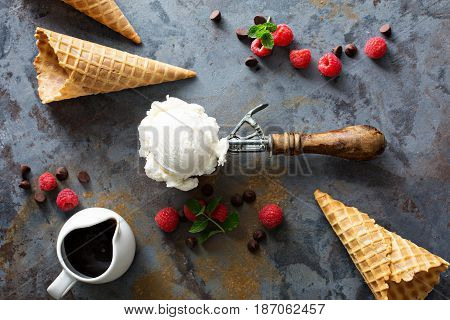 Perfect vanilla ice cream scoop in a spoon with waffles cones and fesh berries