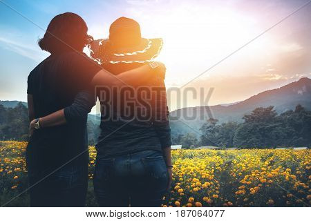 Male and female couples stand in a field of yellow flowers. Evening sun