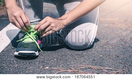 Women tie the chain of jogging shoes. On the runway