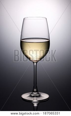 wineglass with half white wine in shadow