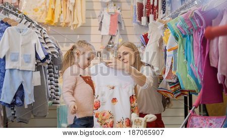 Portrait of a young woman with a daughter that is considering the children's white dress with floral pattern