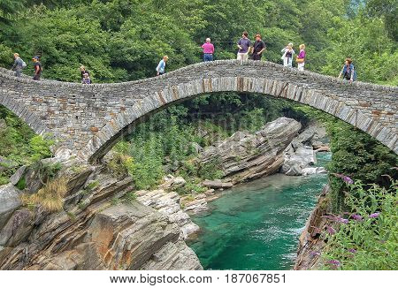 Tourists on one of the two stone arches of the ancient Roman bridge Ponte dei Salti - Val Verzasca, Switzerland, 17 July 2008