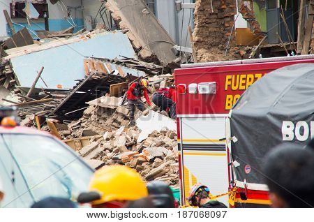 Quito, Ecuador - December 09, 2016: An unidentified firemans in a completely ruined brick building in Quito city with some firetrucks in the damaged area.