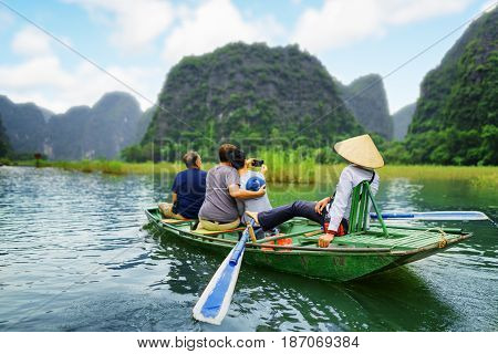 Tourists traveling in boat along the Ngo Dong River and taking selfie at the Tam Coc Ninh Binh Province Vietnam. Rower using her feet to propel oars. Landscape formed by karst towers and rice fields
