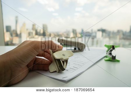 woman use staple puller to remove staple from business document by left hand