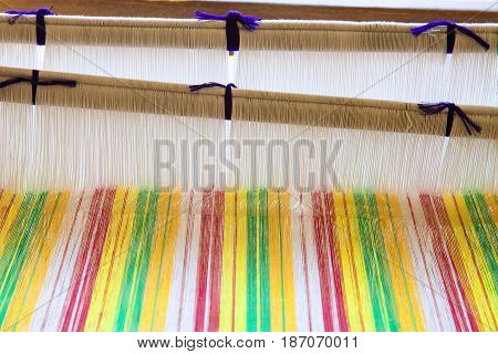 Yarn background old weaving Loom and thread of yarn. A traditional hand-weaving loom being used to make cloth at home.