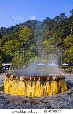 volcanic natural hot spring mineral water pool with steam spa and sun reflect light travel landmark background lampang thailand landscape colorful dark tone Ruksavarin Hot Spring Ranong Thailand.