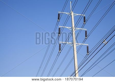 Power pole on stand. Electrical wires on a pole on blue sky background. Electric supply of big city. Land communications.