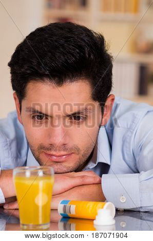Handsome man watching the effervescent tablet in glass of water.