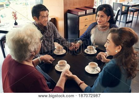 Vietnamese elderly people holding hands when chatting