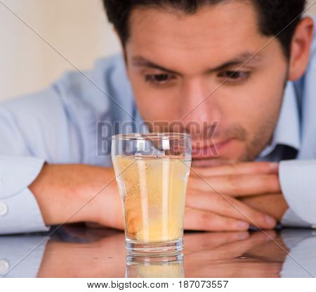 Handsome man watching an effervescent tablet in glass of water dissolving.