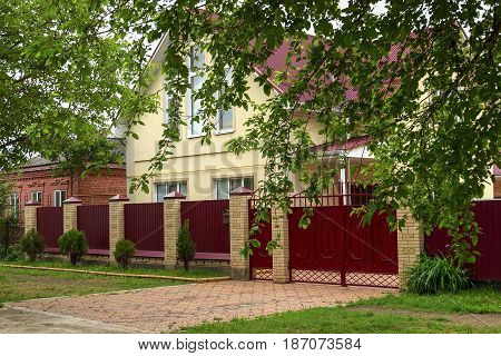 Architecture of a cottage with a metal fence and columns from a brick. The house one-storey with a penthouse. Nearby the one-storey house from a red brick.