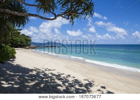 Tropical beach scenery at Andaman sea in Phuket Thailand. Exotic sea view at tropical summer paradise beach of Phuket island with sunny sky and clouds on horizon